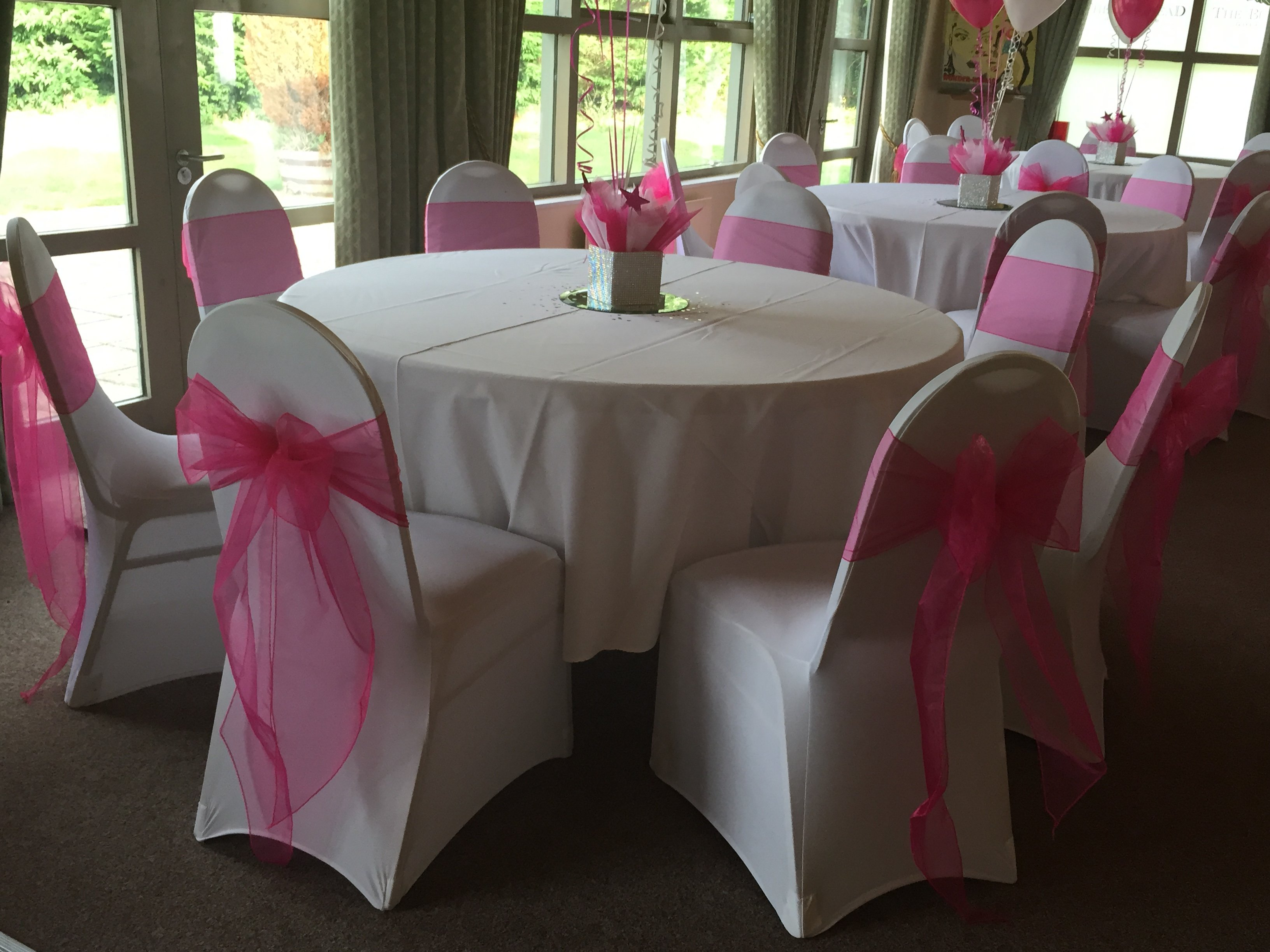 Pink organza sash with white lycra chair covers at Burstead Golf Club