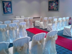 Gold organza sashes with white chair covers at The Holiday Inn Basildon
