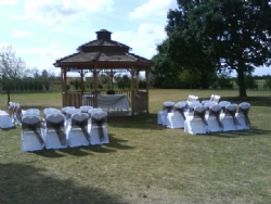 Brown organza sashes with white chair covers at The Old Rectory