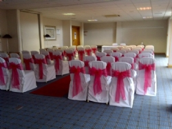 Pink organza sashes and white chair covers and sashes at The Holiday Inn Basildon